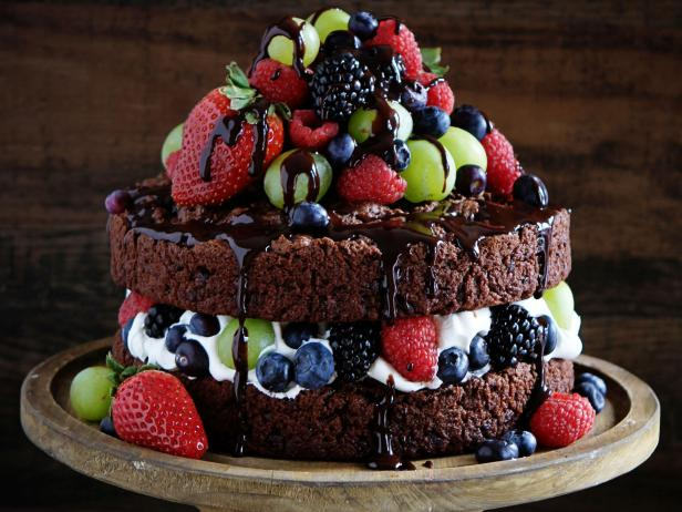 Chocolate cake with cream cheese frosting decorated with berries and chocolate glaze